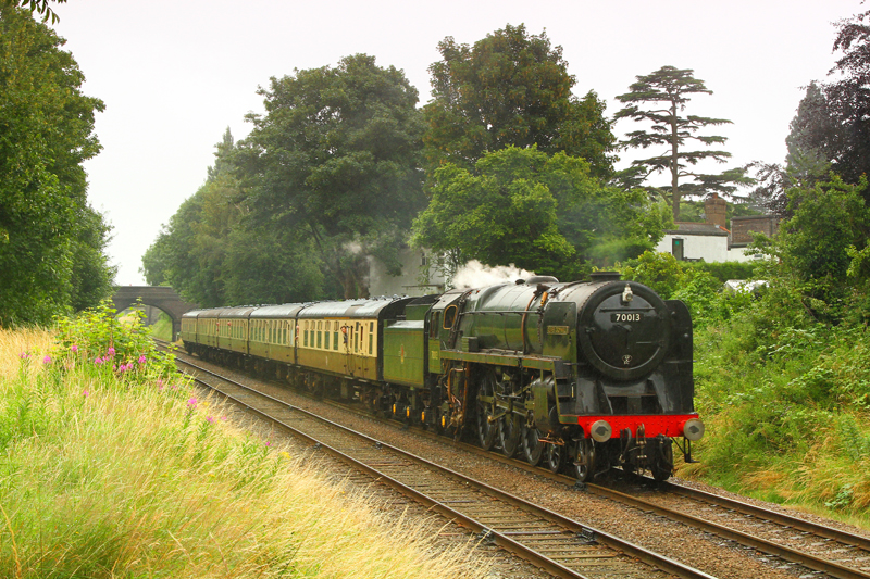 Saturday 16 July 2016. BR Standard Class 7P Britannia 4-6-2 70013 Oliver Cromwell on its first day back in service after major overhaul, drifts downgrade towards Loughborough, Great Central Railway.