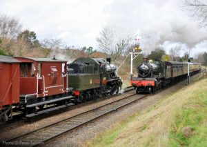 """""""A passenger train powers away from a station stop, while a goods train waits to continue its own journey forward."""" - Photo © Peter Salmon."""