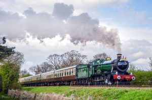 """With locomotive and coaches gleaming, a western express gathers pace on the long straight."" - Photo © Joe Connell."