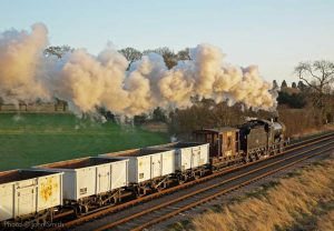 """""""With an LMS 4F in charge, a train of coal empties trundles past as the sun begins to set on another day."""" - Photo © John Smith."""