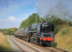 """A passenger train steams southwards in the afternoon sunshine, with 9F 92203 in charge."" - Photo © Martyn Tattam."