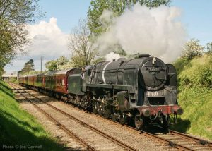 """""""Echoes of the 1960s as a work-stained 9F leads a passenger train towards Leicester North."""" 9F 92214 was specially weathered to present a typical 1960s appearance for a photographic charter. - Photo © Joe Connell."""