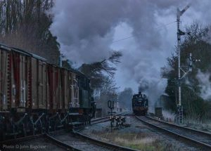 """""""With signal lamps shining brightly, trains pass on a busy main line as nightfall approaches."""" - Photo © John Bagshaw."""