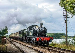 """""""Swithland Reservoir provides a picturesque backdrop as a southbound passenger train steams forward."""" - Photo © Stephen Bottrill."""