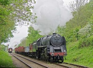 """""""Recreating a scene from the 1960s, a passenger train has just passed a work-stained 9F in charge of a mixed freight, on a busy main line."""" - Photo © Stephen Bottrill."""