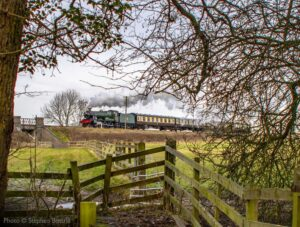 """""""A distant view of a Hall in motion... 6990 'Witherslack Hall' hauls a southbound passenger train, with picturesque countryside along the way."""" - Photo © Stephen Bottrill."""