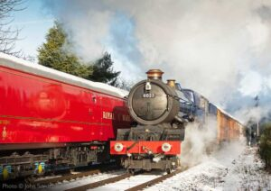 """""""A change of season as a King steams away from a station stop, passing the Travelling Post Office, in snow covered surroundings."""" - Photo © John Smith."""
