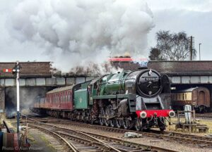 """A spirited departure... 9F 92214 brightens a grey day while steaming away from Loughborough Central."" - Photo © Alan Weaver."