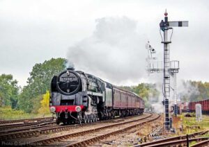 """With power and style, British Railways Standard Class 9F 92214 works a passenger train past Swithland Sidings on the Great Central."" - Photo © Syd Hancock."
