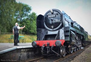 """""""The passengers return... The Signalman's Agent offers the Rothley to Leicester North single line train staff to the crew of 92214, which is hauling our first passenger train since March on 25th July 2020."""" - Photo © Pat Brown."""