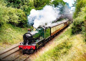 """""""GWR Modified Hall 6990 'Witherslack Hall' works a southbound empty coaching stock train, ready to collect passengers at the next station"""". - Photo © Alan Weaver."""