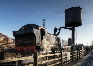 """""""Taking on water before another trip... Visiting GWR 1500 Class 1501 stands at the water column, north of Loughborough Central station"""". - Photo © John Smith."""