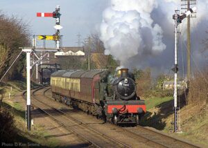 """""""Powering away from the town station... Visiting GWR Manor 7802 'Bradley Manor' steams onto the long straight to begin a gentle climb to the next station"""". - Photo © Ken Simms."""