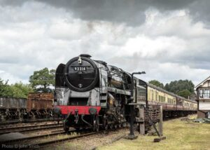 """""""9F 92214 powers away from Quorn & Woodhouse as passenger trains resumed in July 2020, following a temporary pause"""". Photo © John Smith."""