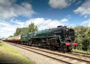 """""""A bright day in Leicestershire as 9F 92214 works a southbound passenger train along the straight, south of Quorn & Woodhouse"""". Photo © John Smith."""