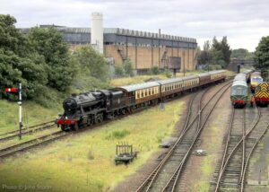 """""""Returning after another trip... Stanier Class 8 48305 arrives at Loughborough Central with empty coaching stock on 29th August 2020, while a diesel railcar is prepared for running on Bank Holiday Monday"""". Photo © John Storer."""