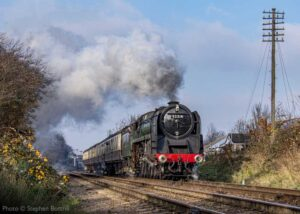 """""""An impressive scene created by the power of a steam locomotive... British Railways Standard Class 9F 92214 accelerates away from Loughborough Central."""" Photo © Stephen Bottrill."""