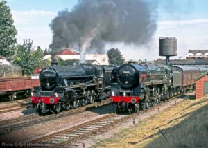 """""""A fine display of motive power at Loughborough Central, as Stanier Class 5 45305 departs with the 'Master Cutler' while Britannia Pacific 70013 'Oliver Cromwell' waits in the siding with stock for the next departure."""" 70013 'Oliver Cromwell' appears courtesy of the National Railway Museum. - Photo © Syd Hancock."""