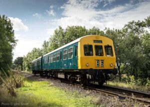 """""""In a scene reminiscent of the late 1960s, a Metro Cammell diesel railcar, recently repainted in the blue livery of British Rail, carries passengers on another journey."""" - Photo © John Smith."""