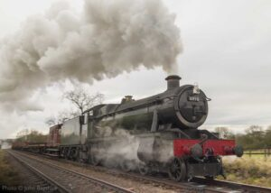 """""""Goods in motion... A dull day is brightened by GWR Modified Hall 6990 'Witherslack Hall', working a mixed goods train."""" - Photo © John Bagshaw."""