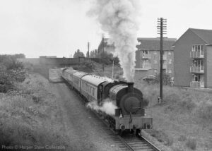 """""""In earlier days of preservation, on 8th July 1977, Littleton Number 5 steams south from Loughborough Central towards Quorn & Woodhouse."""" In the intervening years, double track has been reinstated, and the line has been fully signalled at this location. - Photo © Harper Shaw Collection."""