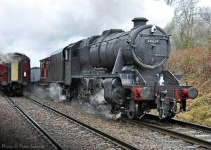 """""""Recreating a scene from the 1960s, work-stained 8F 48624 hauls a coal train along a busy main line."""" - Photo © Peter Salmon."""