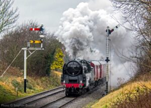 """""""The immense power of a British Railways Standard Class 9F is put to work on a demonstration Travelling Post Office train on the Great Central."""" - Photo © Stephen Bottrill."""