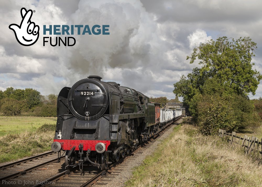 British Railways Standard Class 9F 92214 steams through the Leicestershire countryside, with National Lottery Heritage Fund logo included.