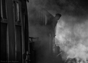 """""""Steam locomotives create an atmosphere all of their own... The Fireman looks back and awaits the 'right away' from the Guard as the train prepares to depart."""" - Photo © John Bagshaw."""