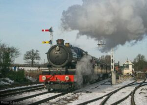 """""""In the snow of early 2013, GWR King 6023 'King Edward II' steams away from Quorn & Woodhouse station with a passenger train."""" - Photo © Joe Connell."""