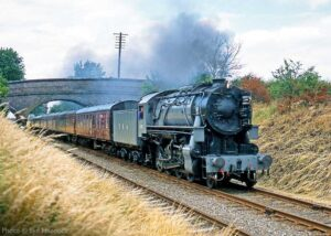 """""""United States Army Transportation Corps S160 2-8-0 5197 steams through the cutting north of Quorn & Woodhouse during an extended visit to the GCR in 2003"""". - Photo © Syd Hancock."""