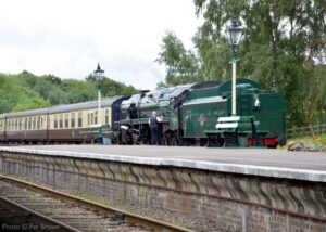 """""""The Train Staff for the single line between Rothley and Leicester North is collected from the footplate crew of 9F 92214 as a passenger train heads north during July 2020."""" - Photo © Pat Brown."""